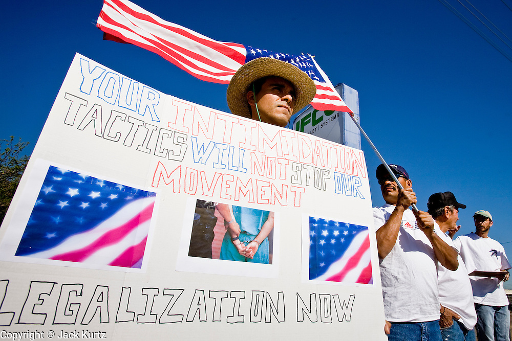 """01 MAY 2006 - PHOENIX, AZ: JORGE PINA, from Tucson, AZ, carries a sign during a demonstration for immigration reform during a """"Day without Immigrants"""" rally in front of IFCO Systems in Phoenix, AZ, May 1. About 50 people gathered at IFCO, a pallet manufacturing business, to demonstrate of favor of immigration reform. IFCO plants across the US were raided by Department of Homeland Security agents two weeks during a sweep against illegal workers. Thirtyfive people were arrested at the IFCO plant in Phoenix.  Photo by Jack Kurtz"""
