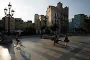 People carrying musical intruments walk down the Prado Avenue along with a girl riding her bicycle in Havana, Cuba on Sunday June 29, 2008.