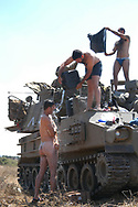 IDF artillery crew step down to take a quick shower out in the field. 2nd Lebanon War. Israel, August 2006.