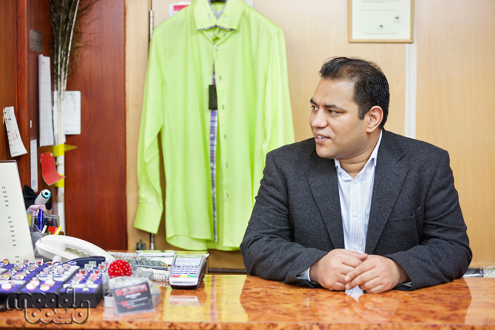 Mid adult male salesperson sitting at desk in menswear store