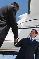 Two mid-adult businessman shaking hands in front of airplane, low angle view.