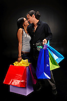 Happy couple with shopping bags in a black background.