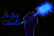 "Hand holding a glowing pen next to ""Je Suis Charlie"" text.Black light"