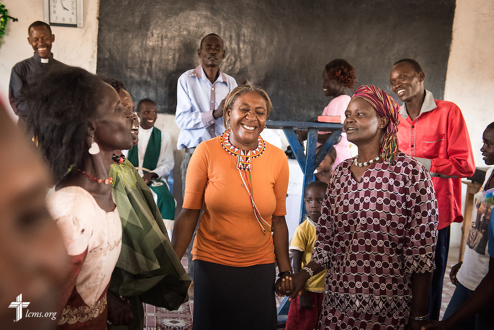 LCMS Missionary Shara Cunningham dances with ladies after she received a gift Photographs at the Lokichar Lutheran congregation of the Evangelical Lutheran Church in Kenya on Thursday, Oct. 15, 2015, in Lokichar, Kenya. LCMS Communications/Erik M. Lunsford