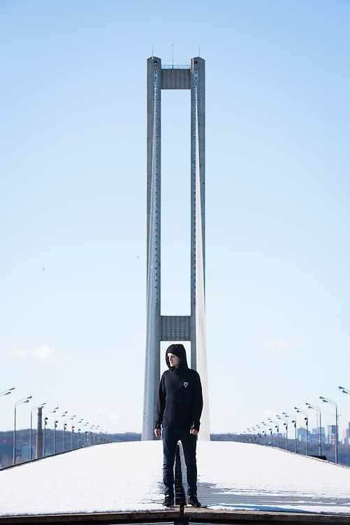 "Extreme climber Mustang Wanted poses for a potrtrait atop a metro tunnel in front of Pivdennyi (""Southern"") Bridge on February 15, 2017 in Kiev, Ukraine. The bridge is one of many structures that he has climbed in Ukraine and elsewhere."