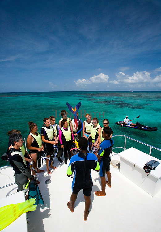 Dive instructor on cruise ship talking to a group of tourists ready to go snorkeling with Hugh Parkey Belize Dive Connection, Belize