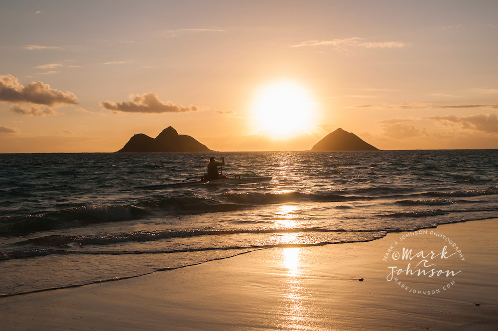 Outrigger canoeist paddling in the early morning, as the sun rises behind the Mokulua Islands, Lanikai, Kailua Bay, Oahu, Hawaii