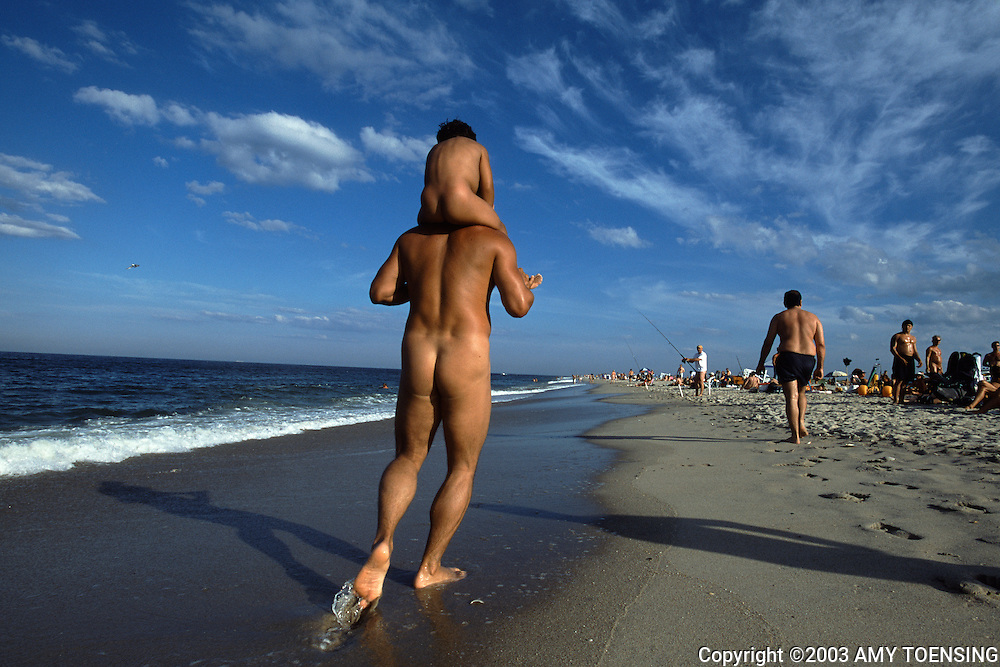 SANDY HOOK, NJ - JULY 12: A nude man and his son take a stroll down through the clothing optional area of Gunnison Beach, July 12, 2003, Sandy Hook, New Jersey. Gunnison is part of the Gateway National Recreational Area and has been a destination for nudists since the 1970s. Many of its visitors have been enjoying the sun and socializing there since its beginning. The Jersey Shore, a 127 mile stretch of coastline known for its variety of beaches, boardwalks, small towns, natural beauty and summer crowds, has been a popular summer destination for over a century. (Photo By Amy Toensing)