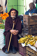 TETOUAN, MOROCCO - 5th April 2016 - Portrait of a local elderly man wearing a traditional Moroccan Djellaba sitting besides fruit and veg for sale in the Tetouan Medina, Rif region of Northern Morocco.