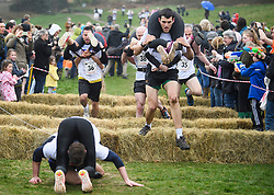 © Licensed to London News Pictures. 08/04/2018. Dorking, UK. A couple faller over during the race. Competitors take part in the 2018 annual Wife Carrying Race in Dorking, Surrey. The race, which is run over a course of 380m, with both men and women carry a 'wife' over obstacles, is believed to have originated in the UK over twelve centuries ago when Viking raiders rampaged into the northeast coast of England carrying off any unwilling local women . Photo credit: Ben Cawthra/LNP