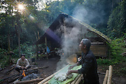 Cooking sticky rice over open fire at jungle campsite, Nam Ha National Protected Area, Luang Namtha, Northern Laos near the Chinese border