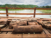 16 SEPTEMBER 2014 - SANGKHLA BURI, KANCHANABURI, THAILAND: Lumber cut from pilings for the reconstruction of the Mon Bridge. The 2800 foot long (850 meters) Saphan Mon (Mon Bridge) spans the Song Kalia River. It is reportedly second longest wooden bridge in the world. The bridge was severely damaged during heavy rainfall in July 2013 when its 230 foot middle section  (70 meters) collapsed during flooding. Officially known as Uttamanusorn Bridge, the bridge has been used by people in Sangkhla Buri (also known as Sangkhlaburi) for 20 years. The bridge was was conceived by Luang Pho Uttama, the late abbot of of Wat Wang Wiwekaram, and was built by hand by Mon refugees from Myanmar (then Burma). The wooden bridge is one of the leading tourist attractions in Kanchanaburi province. The loss of the bridge has hurt the economy of the Mon community opposite Sangkhla Buri. The repair has taken far longer than expected. Thai Prime Minister General Prayuth Chan-ocha ordered an engineer unit of the Royal Thai Army to help the local Mon population repair the bridge. Local people said they hope the bridge is repaired by the end November, which is when the tourist season starts.    PHOTO BY JACK KURTZ