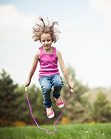 Young girl skipping in park
