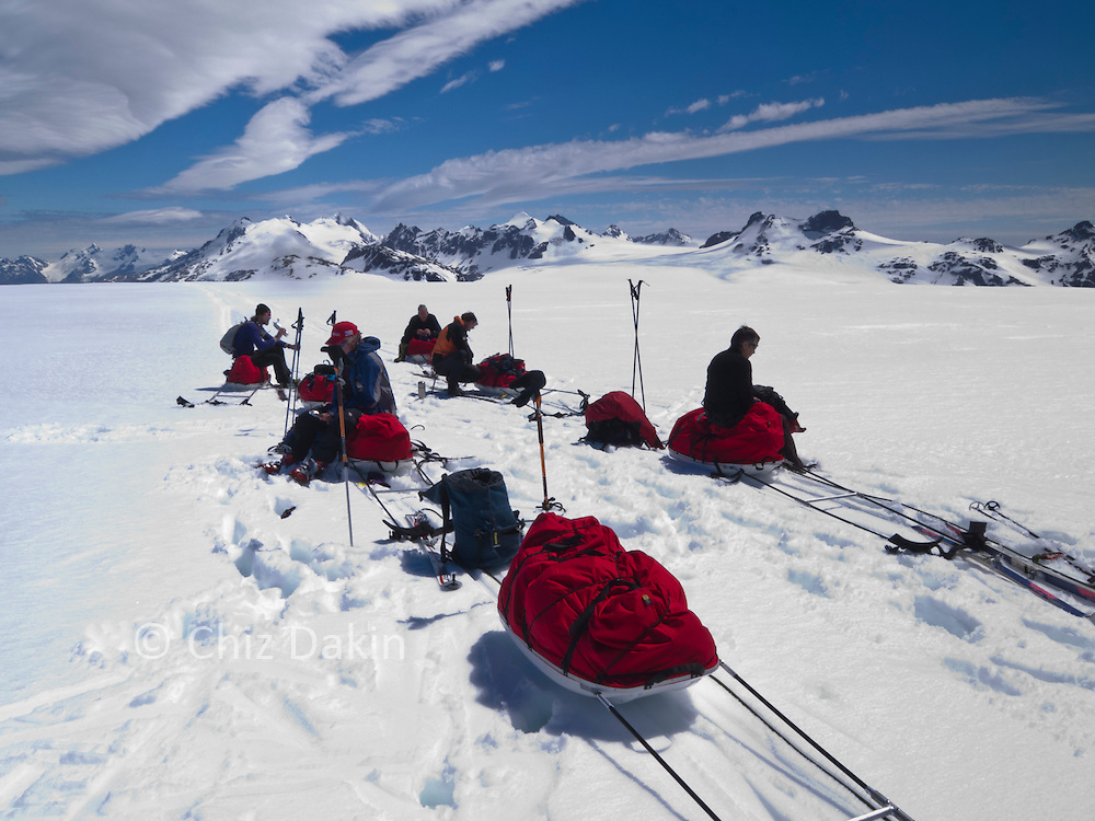 Ski-mountaineering team sitting on pulkas (sledges) while taking a short break on the Murray Snowfield (Shackleton's Traverse, South Georgia)