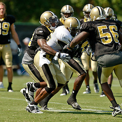 July 31, 2010; Metairie, LA, USA; New Orleans Saints running back Reggie Bush (25) runs into a crowd of defenders during a training camp practice at the New Orleans Saints practice facility. Mandatory Credit: Derick E. Hingle