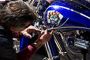May 10, 2013 – New York, NY. A man works on a custom pin strip job on a bike at the Harley Davidson dealership in Queens. 05/10/2013 Photograph by Jeanette D. Moses/NYCity Photo Wire