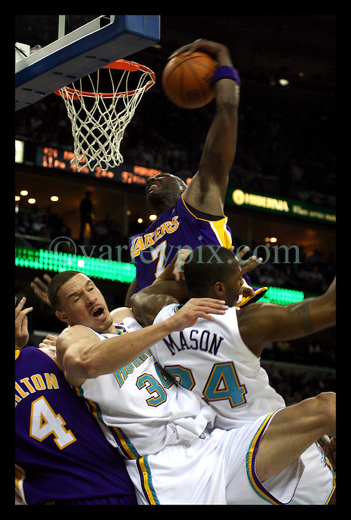 March 8th, 2006. New Orleans, Louisiana. Six months after hurricane Katrina the New Orleans Arena hosts its first professional basketball game with the local Hornets against the Lakers. The arena was packed for the event with fans delighted to have their team back in town. LA Laker's Lamar Odom knocks aside Hornet's Desmond Mason to score.