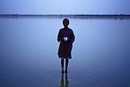 Mali boy collecting a drink of water at twilight from a shallow lake in the Tessit area.