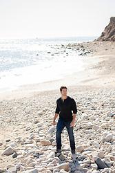 hot man walking on a rocky beach