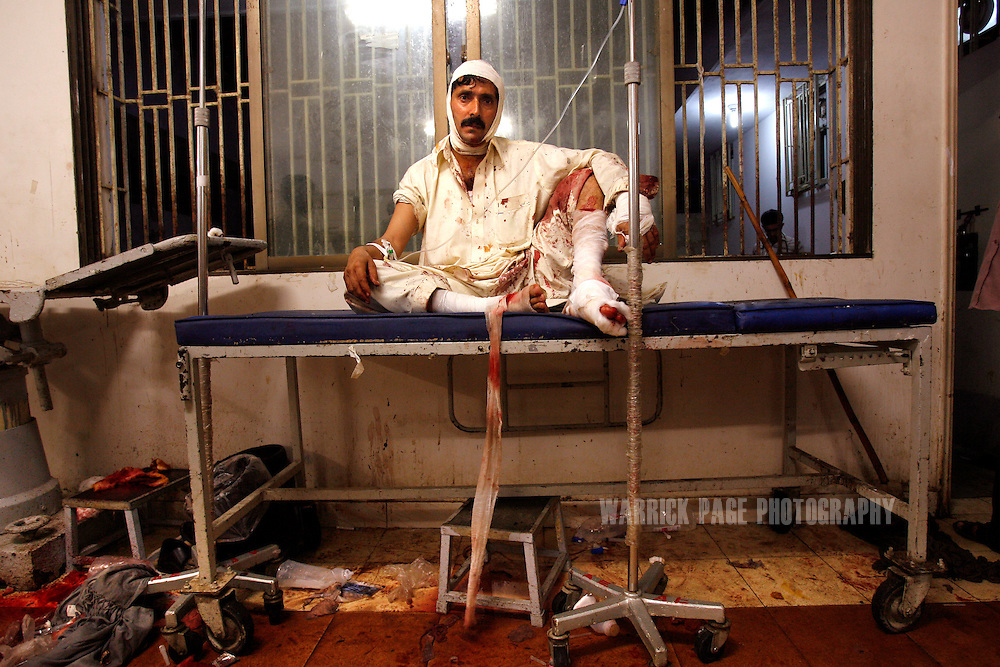 KARACHI, PAKISTAN - OCTOBER 19: A wounded man sits in shock above the blood-soaked floor at Jinnah Medical Centre, October 19, 2007, Karachi, Pakistan. At least 140 people were killed in a suicide bombing aimed at assassinating former prime minister and opposition leader, Benazir Bhutto. Bhutto was unharmed in the Karachi blast, only to be gunned down two months later by an unknown assassin at an election rally in the garrison city of Rawalpindi on December 27. Bhutto returned to Pakistan after 7 years in self-imposed exile on a US-brokered power-sharing deal with President Musharraf. The deal collapsed after Musharraf implemented emergency rule in November, arresting and imprisoning thousands of opposition members and lawyers. During her short-lived campaign, Bhutto had vowed to restore civilian leadership and democracy, and crush Islamic militancy throughout the country. (Photo by Warrick Page)