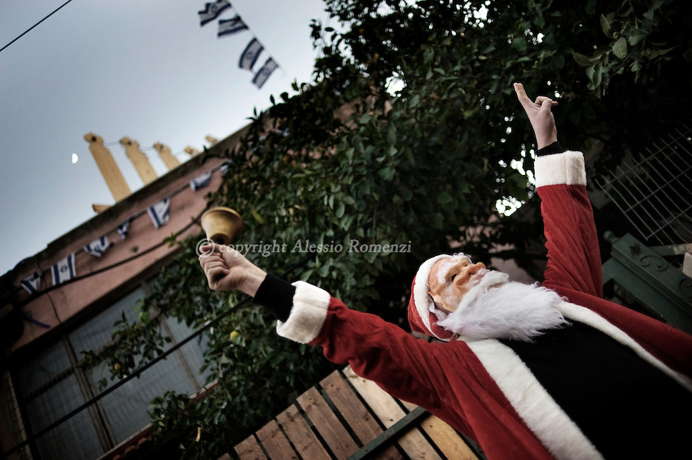 A Palestinian Santa Claus rings a bell in front of Israeli border policemen outside one of the disputed houses occupied by Israeli settlers in the Arab Sheikh Jarrah neighborhood in East Jerusalem, on December 23, 2009..© ALESSIO ROMENZI