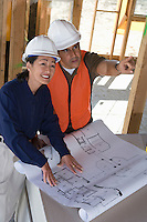 Architect and construction worker looking up at ceiling with blueprints on table inside half constructed house