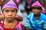 "11 MAY 2013 - BANGKOK, THAILAND:   The children of farmers wear pink bandanas like their parents did during a protest at Government House. Several hundred small scale family farmers camped out ""Government House"" (the office of the Prime Minister) in Bangkok to Thai Prime Minister Yingluck Shinawatra to deliver on her promises to improve the situation of family farmers. The People's Movement for a Just Society (P-move) is a network organization which aims strengthen the voices of different, but related causes working to bring justice for marginalized groups in Thailand, including land rights for small-scale farmers, citizenship for stateless persons, fair compensation for communities forced to relocate to accommodate large scale state projects, and housing solutions for urban slum dwellers, among others.   PHOTO BY JACK KURTZ"