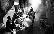 Ab Afghan man spreads incense in a slaughter house within the Old City,  Peshawer Pakistan January 2002....