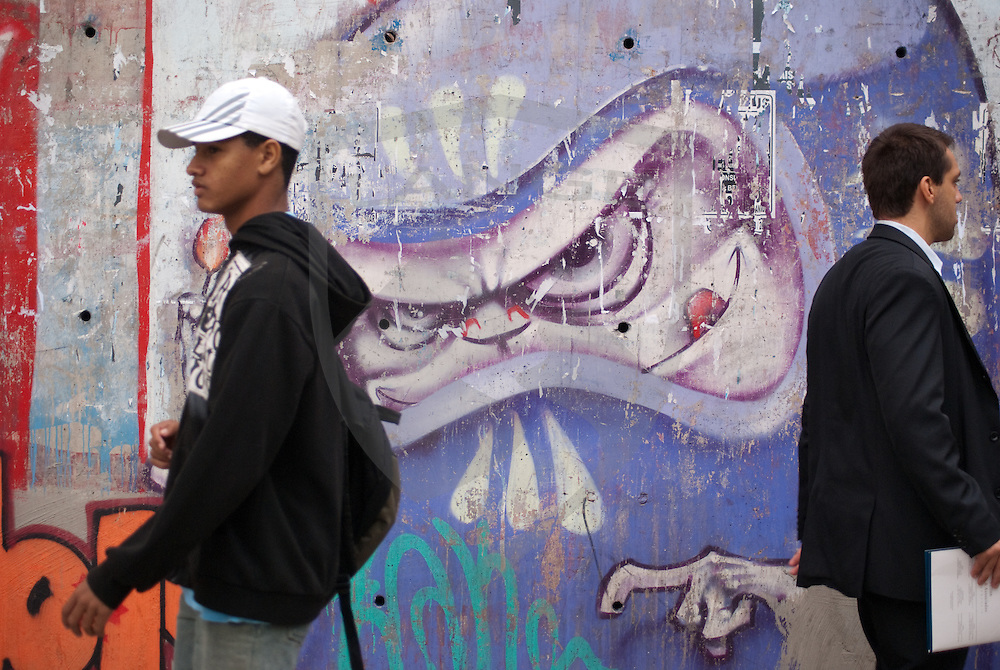 a young urban professional and ethnic brazilian walk away from one another with an evil graffiti visage behind, seeming to exemplify the divergent paths of economic disparity and the dissent that separates them.