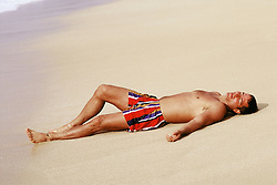 Man in bathing suit lying on sand at beach