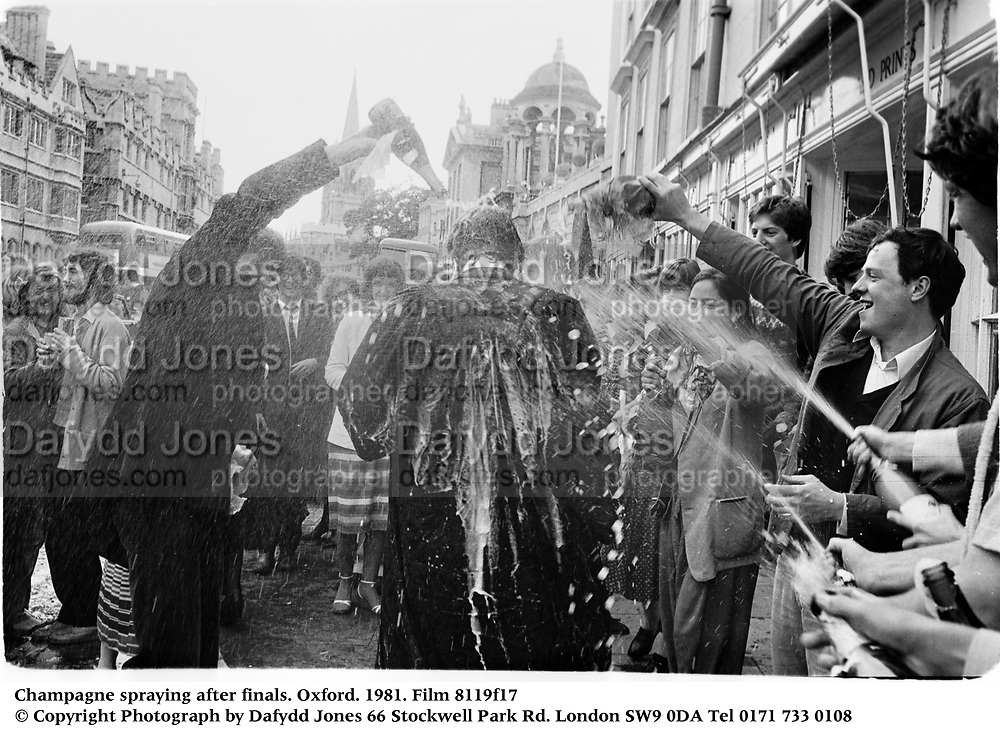 Champagne spraying after finals. Oxford. 1981. Film 8119f17<br />© Copyright Photograph by Dafydd Jones<br />66 Stockwell Park Rd. London SW9 0DA<br />Tel 0171 733 0108