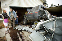 JEROME A. POLLOS/Press..Tony Bauer and Caroline Marienau survey the damage to their truck as it is dragged out of their garage Monday morning in Coeur d'Alene.  Eric Marienau, Caroline Marienau's ex-husband, repeatedly rammed into the garage with his truck which was loaded with gas cans rigged as fire bombs.