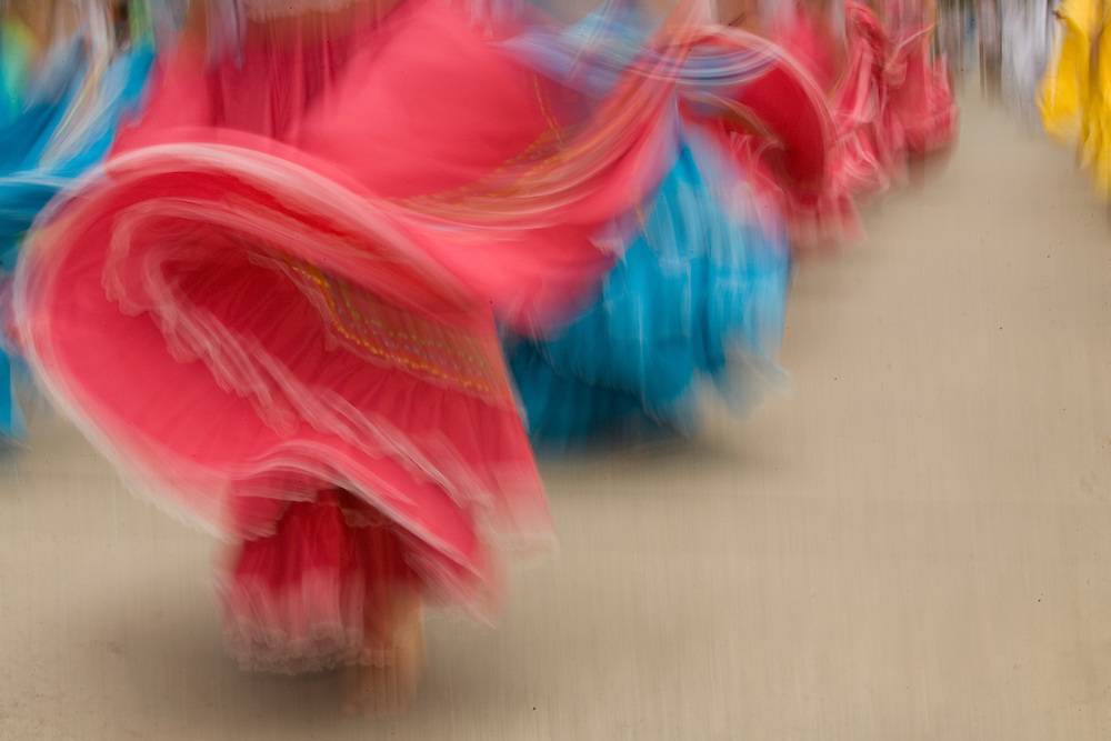 South America, Ecuador, Cuenca.  Swirling skirt of female dancers in folklore troupe during annual parade and festival to celebrate founding of Cuenca in 1557.  Cuenca is a UNESCO World Heritage Site.