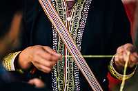 A young Red Dao woman works on an embroidery.