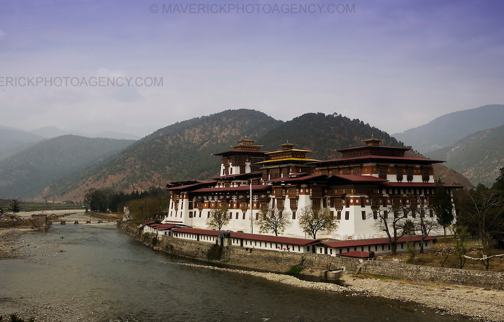 Punakha dzong  (palace of great happiness) situated at the point where two rivers meet, Punakha..Commonly described as the last Himalayan Shangrila, Bhutan is a country of unique serenity, harmony, and beauty. Nestled between India, China, and Tibet, this independent country whose name translates as 'the Land of the Thunder Dragon' has for the past 300 years  proactively followed a policy of isolation and cultural protection. Travel in and out of the country is strictly regulated, and the impact of outside influences on the local culture is carefully monitored. Spirituality is an important aspect of Bhutanese culture, with Buddhism being interlinked with everyday life. Gross National Happiness (GNH), as opposed to GNP/GDP, forms the cornerstone of its development strategy which focuses on a holistic development strategy that complements its cultural and Buddhist spiritual values.