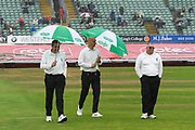 The umpires out on the field for the 2:30 inspection walk off with umbrellas up as heavy rain falls again to further the delay the start of play during the Specsavers County Champ Div 1 match between Somerset County Cricket Club and Essex County Cricket Club at the Cooper Associates County Ground, Taunton, United Kingdom on 25 September 2019.
