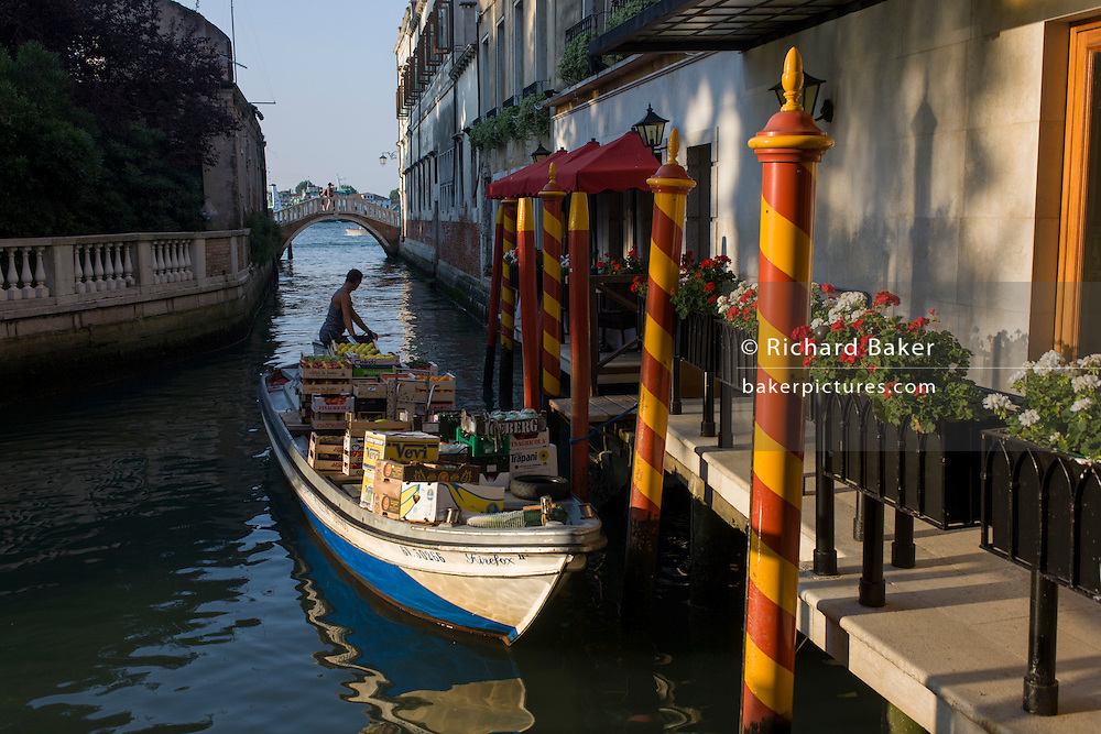 Delivery man reverses back from jetty, back on to Grand Canal after dropping off supplies in Venice, Italy.