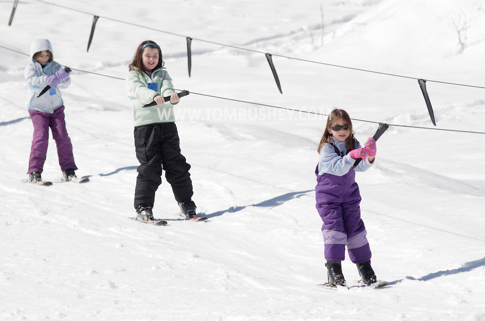 Bridgeville, New York - Three girls use the tow rope on a beginners' slope at Holiday Mountain on March 6, 2010.