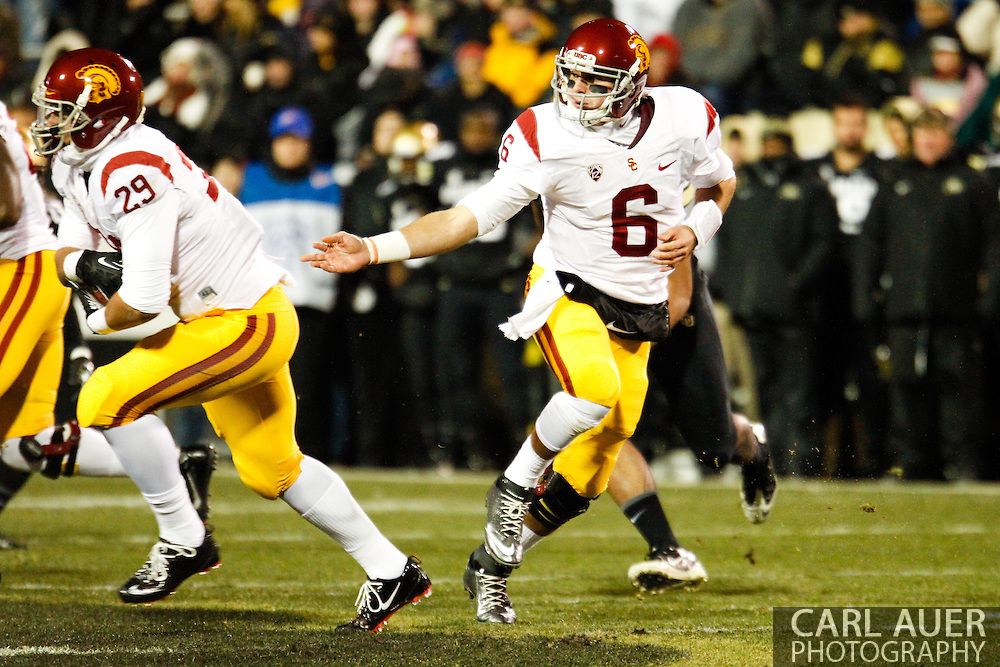 November 23rd, 2013:  USC Trojans sophomore quarterback Cody Kessler (6) hands the ball off to freshman running back Ty Isaac (29) in the second quarter of the NCAA Football game between the University of Southern California Trojans and the University of Colorado Buffaloes at Folsom Field in Boulder, Colorado