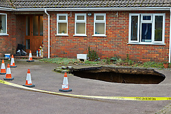 © Licensed to London News Pictures.  03/02/2014. BUCKINGHAMSHIRE, UK. A large sinkhole, 30ft deep and with a VW Lupo car at the bottom, has appeared outside a family home in Walter's Ash, near High Wycombe in Buckinghamshire. The area has a history of mining and, along with the rest of the UK, experienced heavy rainfalls over the last month. Photo credit: Cliff Hide/LNP
