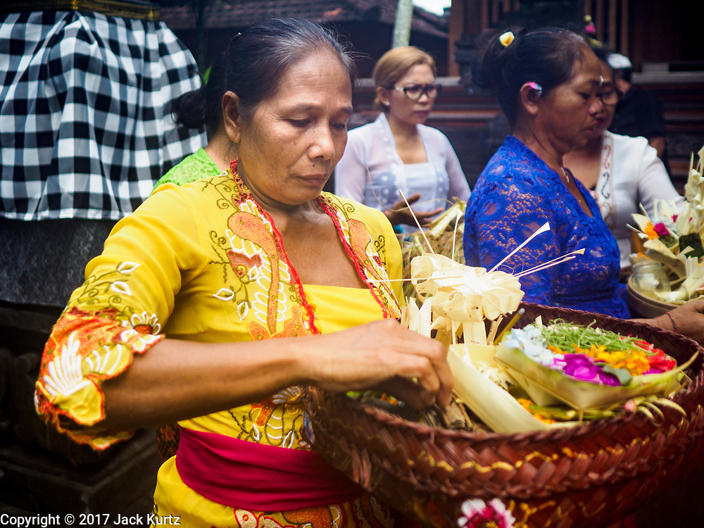 "08 AUGUST 2017 - UBUD, BALI, INDONESIA: Women participate in a ceremony to honor a family temple in Ubud, Bali. Balinese Hindus have a 210 day calender and every almost every family compound on Bali has a family temple. Once a year (or every 210 days) families celebrate the ""birthday"" of their temple with a ceremony.     PHOTO BY JACK KURTZ"