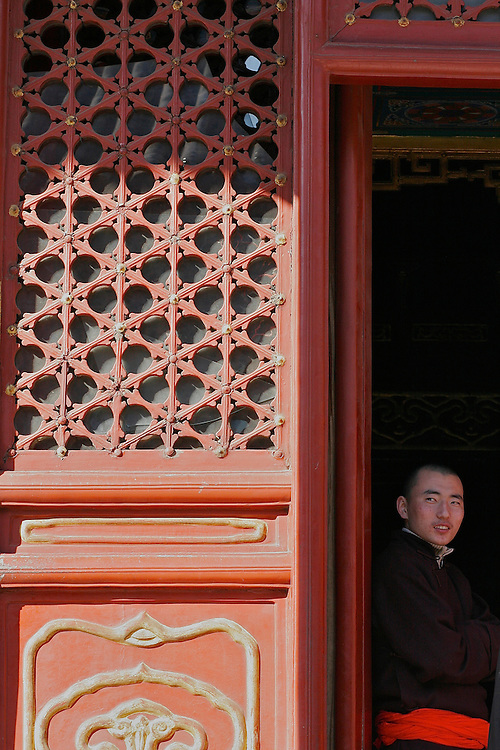 Standing in the doorway of a hall at Yonghegong is a young monk.  This Tibetan Temple is known to tourists as Lama Temple and it's located in Dongcheng District Beijing, China. This is the largest Temple of its kind outside of Tibet.  In 1723 the structure was turned into a Temple after the resident became the third Qing Emperor.