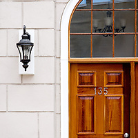 A panelled wooden door with outside wall light