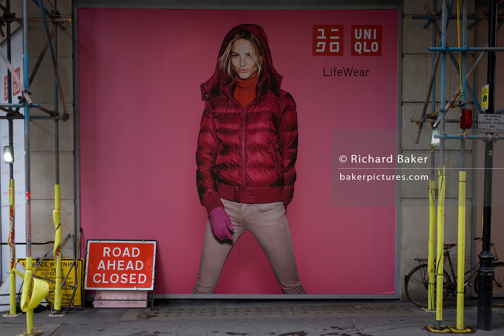 Road Closed Ahead sign and clothes model advertising retailer Uniqlo in a side-street in central London.