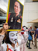 "14 JULY 2013 - BANGKOK, THAILAND: A protesters carries a portrait of Bhumibol Adulyadej, the King of Thailand, during a White Mask protest in Bangkok Sunday. About 150 members of the so called ""White Mask"" movement marched through the central shopping district of Bangkok Sunday to call for the resignation of Yingluck Shinawatra, the Prime Minister of Thailand. The White Mask protesters are strong supporters of the Thai monarchy. They claim that Yingluck is acting as a puppet for her brother, former Prime Minister Thaksin Shinawatra, who was deposed by a military coup in 2006 and now lives in exile in Dubai.       PHOTO BY JACK KURTZ"