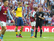 Referee Jon Moss talks to aston villa Fabian Delph during the The FA Cup match between Arsenal and Aston Villa at Wembley Stadium, London, England on 30 May 2015. Photo by Phil Duncan.