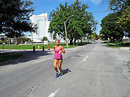 A lone woman runs  down the middle of  a usually busy street during the second Open Streets festival, Windsor, Canada.