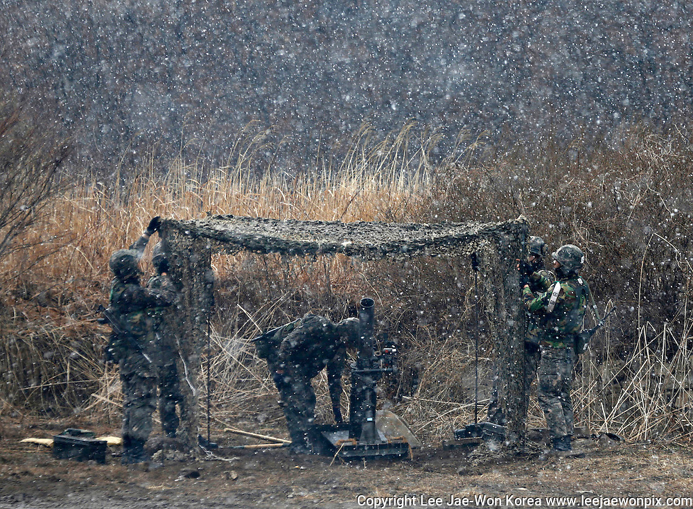 South Korean soldiers of an artillery unit check their gears during a drill as it snows in Hwacheon, about 20 km (12 miles) south of the demilitarized zone separating the two Koreas and about 120 km (75 miles) northeast of Seoul. Photo by Lee Jae-Won (SOUTH KOREA) www.leejaewonpix.com/