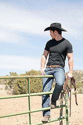 cowboy sitting on a ranch gate