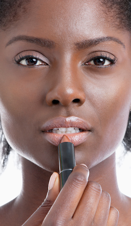 Close-up portrait of young African American woman applying lipstick